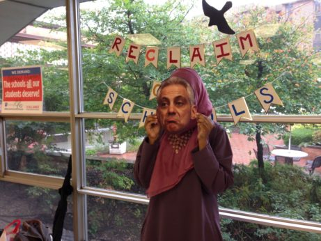 After filling out two postcards addressed to her state lawmakers urging them to fund MAP grants and education, an NEIU student dons a Mayor Rahm Emanuel mask for a photo booth protest shot to be posted on social media. | Teresa Albano / PW