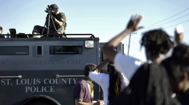A member of the St. Louis County Police Department points his weapon in the direction of a group of protesters in Ferguson, Mo., on August 10, 2014. | Jeff Roberson / AP