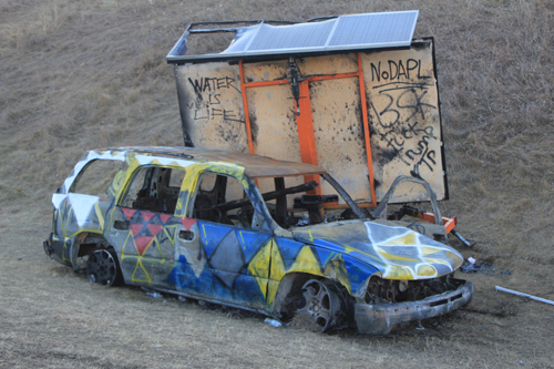 Anti-Trump graffiti spotted on abandoned vehicle near police barricade. Michelle Zacarias } PW