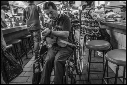 A violinist in his wheelchair checks his watch after getting a bite to eat.  Maybe he has a spot in the market to play for only a certain time, and can't be late. | David Bacon