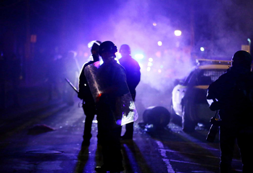 In this Nov. 25, 2014 file photo, police officers watch protesters as smoke fills the streets in Ferguson, Mo. | Charlie Riedel / AP