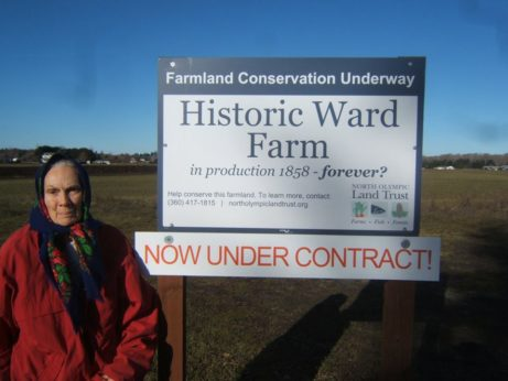 Joyce Wheeler stands next to the sign announcing the conservation of Historic Ward Farm in Washington. | Tim Wheeler / PW