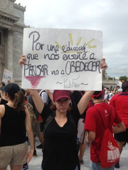 "A university student participates in a demonstration in San Juan. Her sign features a quote from Paulo Freire, author of ""Pedagogy of the Oppressed,"" which says, ""For an education that teaches us to think, not to obey."" 